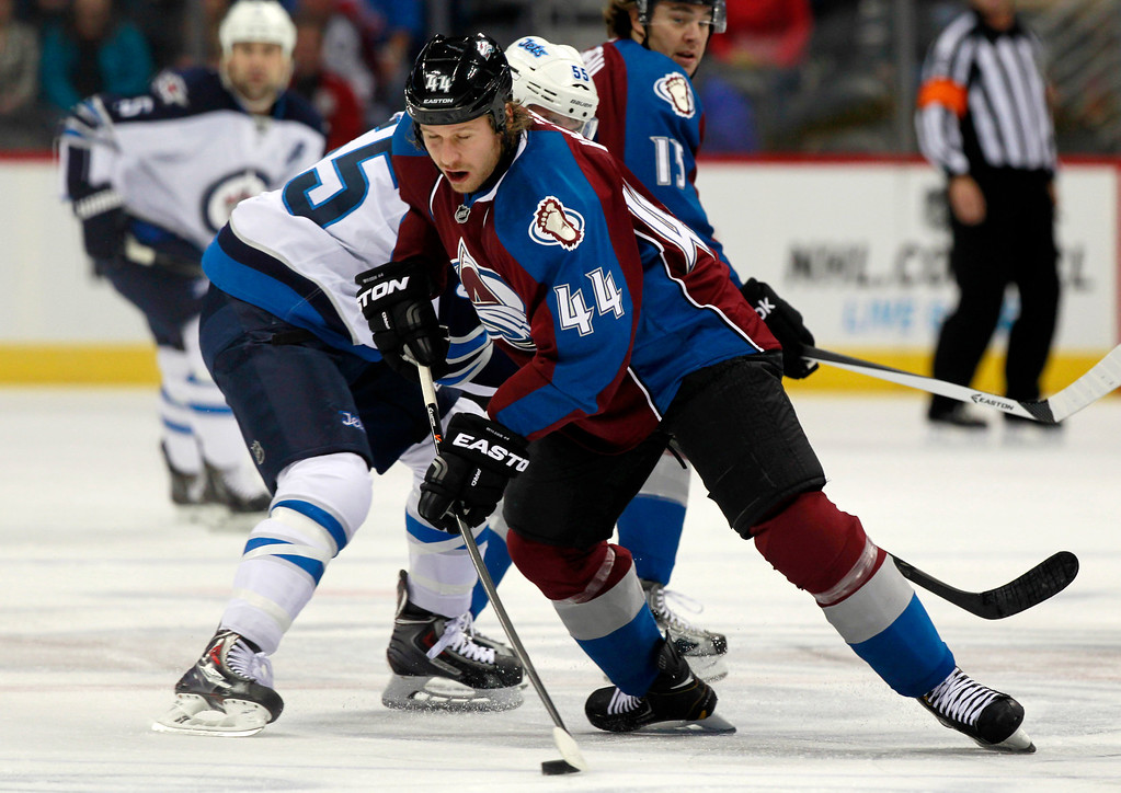 . Colorado Avalanche defenseman Ryan Wilson, front, tries to pick up a loose puck as Winnipeg Jets center Mark Scheifele covers in the first period of an NHL hockey game in Denver on Sunday, Oct. 27, 2013. (AP Photo/David Zalubowski)
