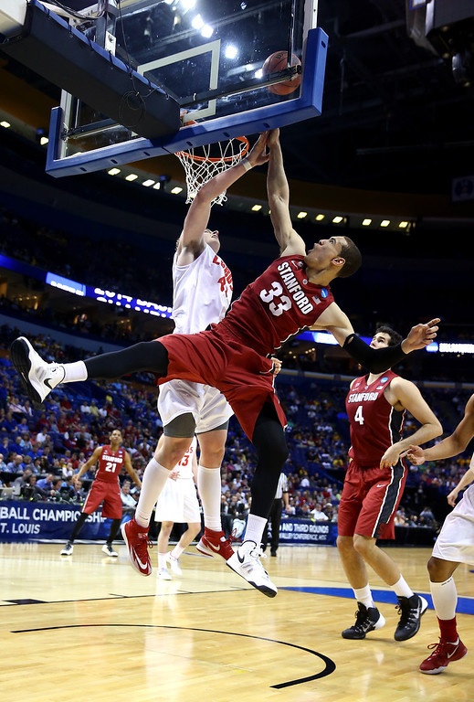 . Dwight Powell #33 of the Stanford Cardinal gets fouled by Cameron Bairstow #41 of the New Mexico Lobos during the second round of the 2014 NCAA Men\'s Basketball Tournament at Scottrade Center on March 21, 2014 in St Louis, Missouri.  (Photo by Andy Lyons/Getty Images)