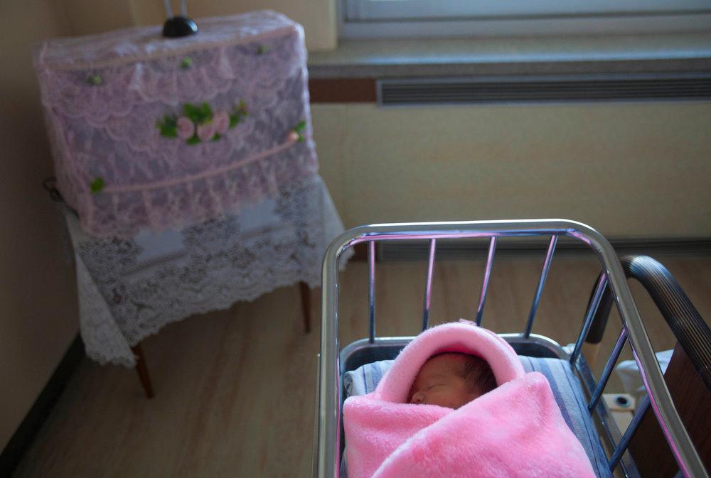 Description of . A newborn North Korean baby girl lies in crib in her mother's hospital room inside Pyongyang Maternity Hospital in Pyongyang, North Korea on Tuesday Oct. 11, 2011.  (AP Photo/David Guttenfelder)