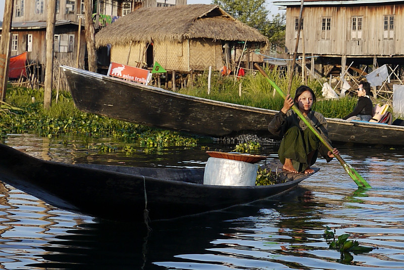 A young woman with thanaka rowing on Inle Lake, Burma (Myanmar).