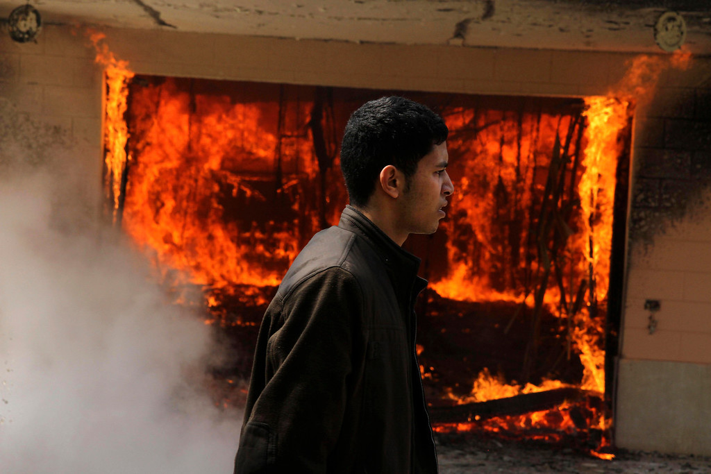 . An Egyptian man walks on the grounds of a police officer\'s club as a fire set by protesters burns in Cairo, Egypt, Saturday, March 9, 2013. (AP Photo/Ahmed Gomaa)