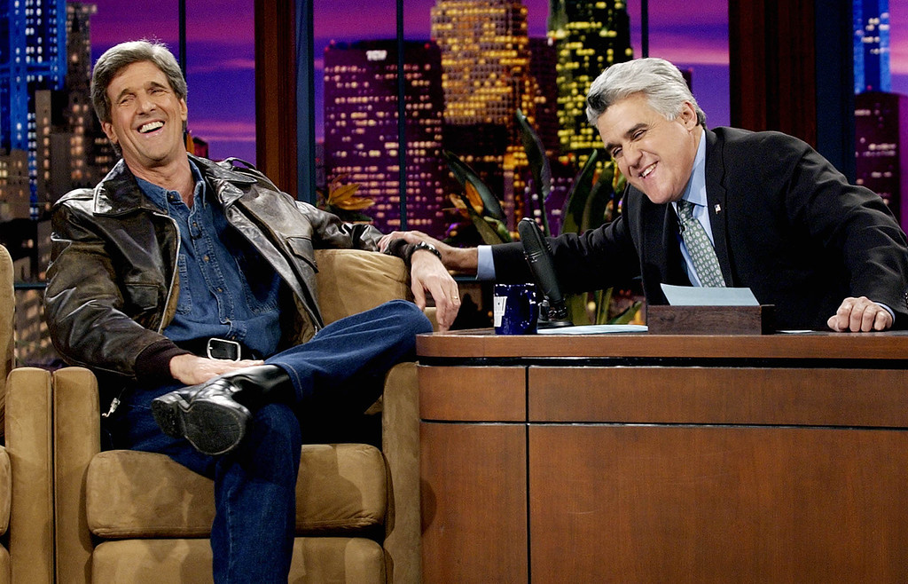 """. Wearing a leather jacket over a denim shirt and pants that he wore while making his entrance driving a motorcycle onstage, presidential candidate Sen. John Kerry, D-Mass., shares a laugh with \""""Tonight Show\"""" host Jay Leno at NBC studios in Burbank, Calif., Tuesday, Nov. 11, 2003.  (AP Photo/Reed Saxon)"""