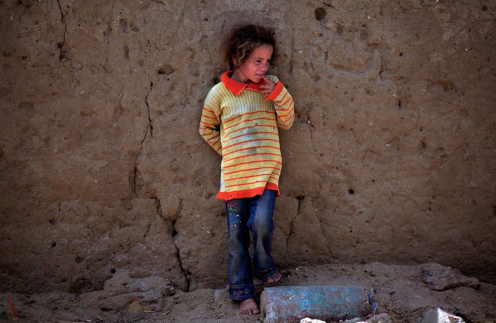 . A Palestinian refugee stands by a mud wall in Gezirat al-Fadel village, Sharqiya, about 150 kilometers (93 miles) east of Cairo, Egypt on Friday, May 17, 2013.  (AP Photo/Khalil Hamra)