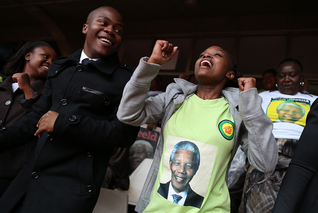 . JOHANNESBURG, SOUTH AFRICA - DECEMBER 10:  People sing and dance while attending a telecast of the Nelson Mandela memorial service at Ellis Park on December 10, 2013 in Johannesburg, South Africa. Over 60 heads of state have travelled to South Africa to attend a week of events commemorating the life of former South African President Nelson Mandela. Mr Mandela passed away on the evening of December 5, 2013 at his home in Houghton at the age of 95. Mandela became South Africa\'s first black president in 1994 after spending 27 years in jail for his activism against apartheid in a racially-divided South Africa.  (Photo by Justin Sullivan/Getty Images)