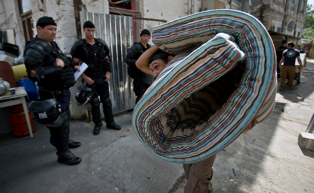 . A Roma man carries belongings into the street as riot policemen watch whilst more than 100 people are evicted from their homes in Bucharest, Romania, Monday, Sept. 15, 2014. (AP Photo/Vadim Ghirda)