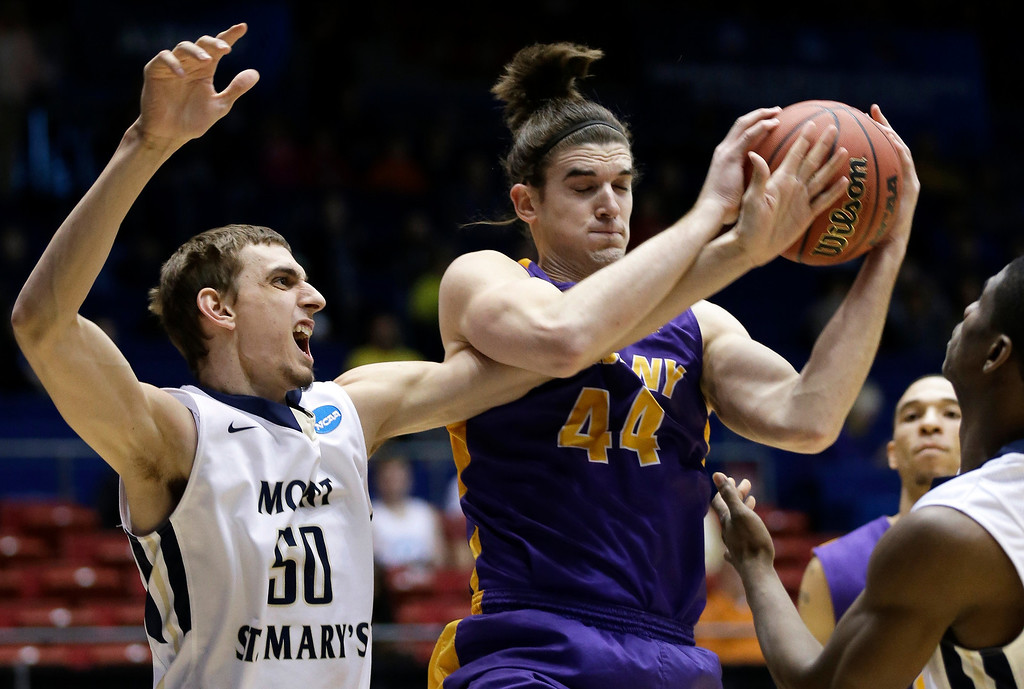 . Albany center John Puk (44) pulls a rebound away from Mount St. Mary\'s center Taylor Danaher (50) in the first half of a first-round game of the NCAA college basketball tournament, Tuesday, March 18, 2014, in Dayton, Ohio. (AP Photo/Al Behrman)