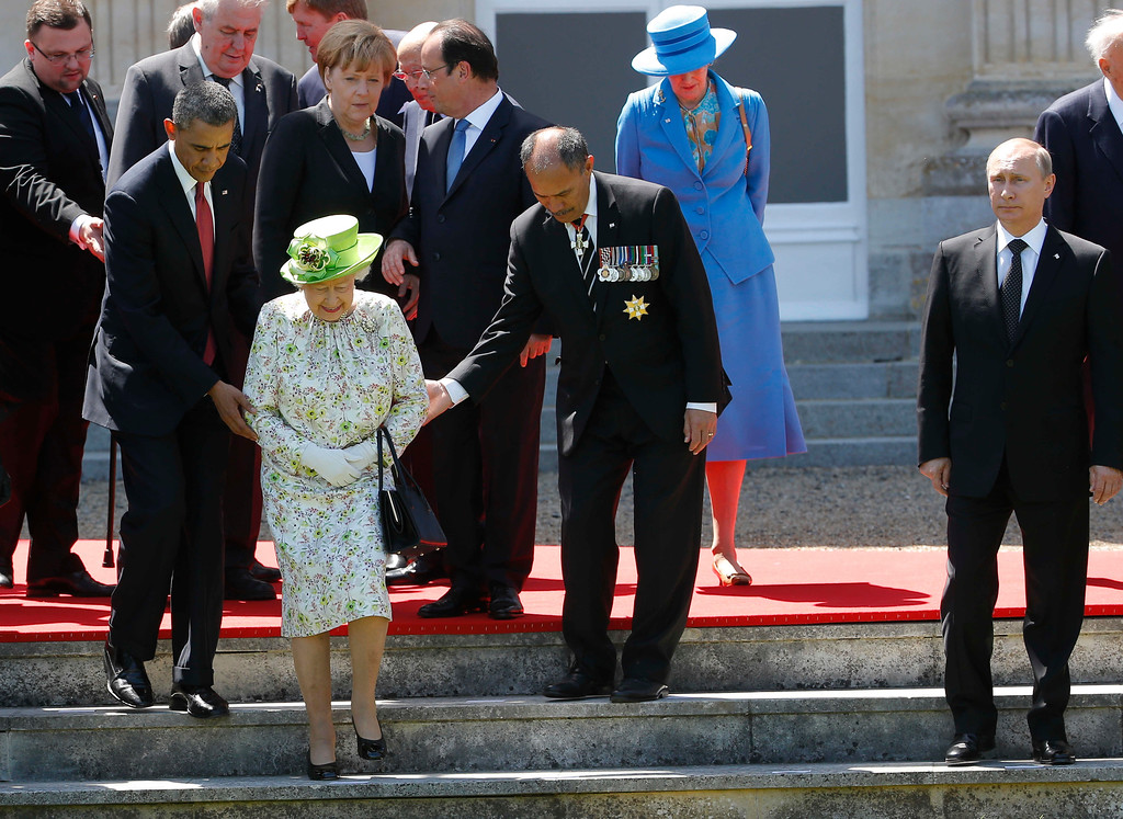 . Russian President Vladimir Putin stands at right as U.S. President Barack Obama, left, and New Zealand\'s Governor-General Jerry Mateparae guide Britain\'s Queen Elizabeth II to her position for a group photo, with French President Francois Hollande, in the background, talking with German Chancellor Angela Merkel, as they take part in commemorations for  the 70th anniversary of the D-Day landings,  in Benouville in Normandy, France, Friday, June 6, 2014. (AP Photo/Charles Dharapak)