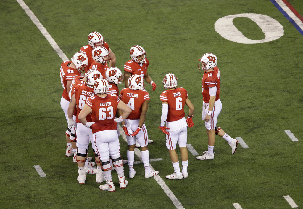 . Wisconsin quarterback Alex Hornibrook (12) talks with his team during the first half of the Big Ten championship NCAA college football game against Ohio State, Saturday, Dec. 2, 2017, in Indianapolis. (AP Photo/AJ Mast)