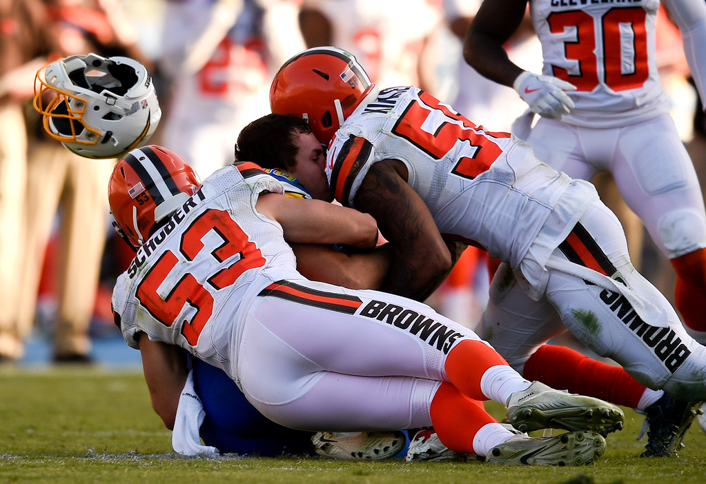 . Los Angeles Chargers tight end Hunter Henry, middle, loses his helmet while being is tackled by Cleveland Browns linebacker Deon King, top and middle linebacker Joe Schobert during the second half of an NFL football game Sunday, Dec. 3, 2017, in Carson, Calif. (AP Photo/Kelvin Kuo)