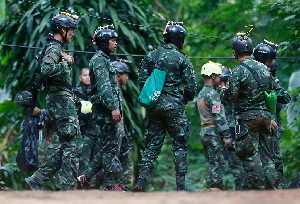 . Thai rescuers prepare to enter the cave where 12 boys and their soccer coach have been trapped since June 23, in Mae Sai, Chiang Rai province, in northern Thailand Friday, July 6, 2018. Thai authorities are racing to pump out water from the flooded cave before more rains are forecast to hit the northern region. (AP Photo/Sakchai Lalit)