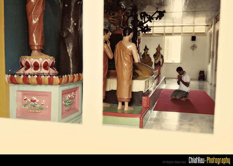 While I am walking outside I found that there is a man doing his praying inside the temple... so I decided to go for a shot here.