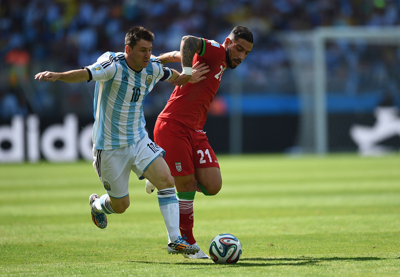 . Argentina\'s forward and captain Lionel Messi (L) and Iran\'s forward Ashkan Dejagah vie during the Group F football match between Argentina and Iran at the Mineirao Stadium in Belo Horizonte during the 2014 FIFA World Cup in Brazil on June 21, 2014.  (BEHROUZ MEHRI/AFP/Getty Images)