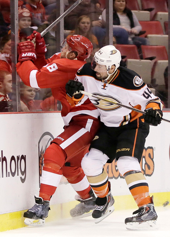 . Detroit Red Wings\' Joakim Andersson (18), of Sweden, is checked against the boards by Anaheim Ducks\' Nate Thompson (44) during the first period of an NHL hockey games Saturday, Oct. 11, 2014, in Detroit. (AP Photo/Duane Burleson)