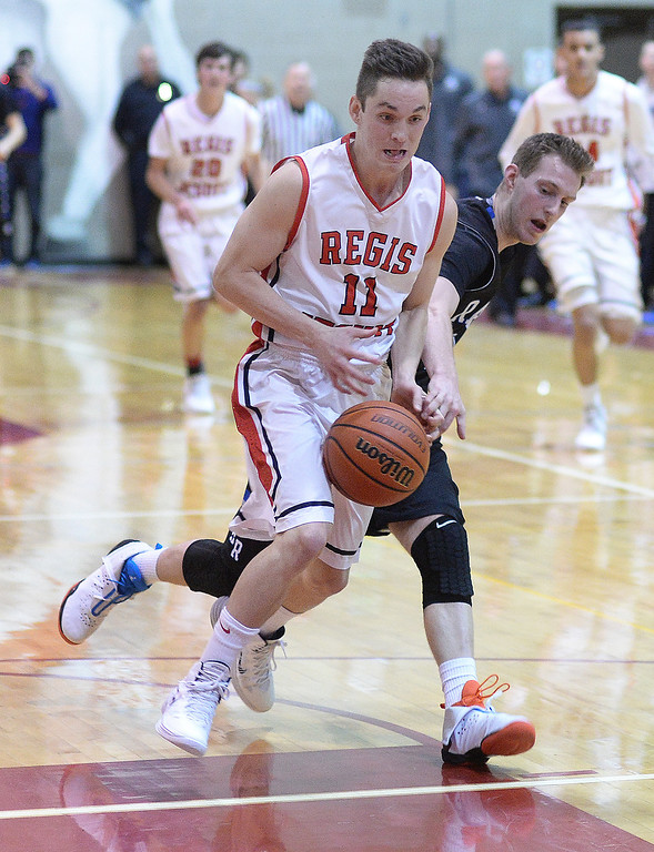 . Regis senior guard Zach Smith (11) raced Falcons\' guard Ryley Stewart (13) to the ball in the first half. The Regis Jesuit High School boy\'s basketball team defeated Highlands Ranch 63-54 Tuesday night, February 4, 2014. Photo By Karl Gehring/The Denver Post