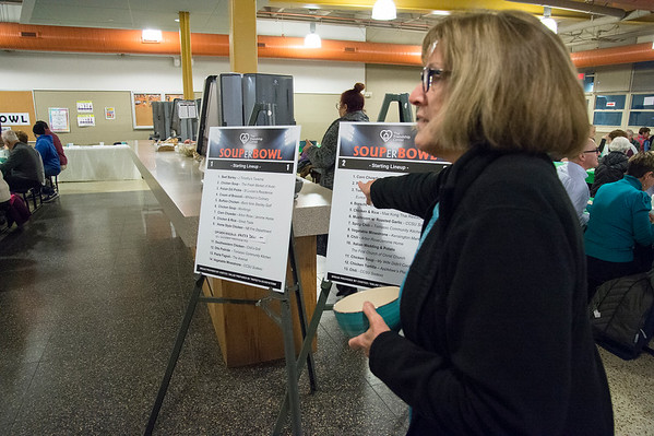 01/30/20 Wesley Bunnell | StaffrrThe annual SOUPerBowl to benefit the Friendship Centers Soup Kitchen took place on Thursday Jan 30, 2020 at E.C. Goodwin Technical School. Marie Ortiz points out the choices of soup to her friends in attendance.