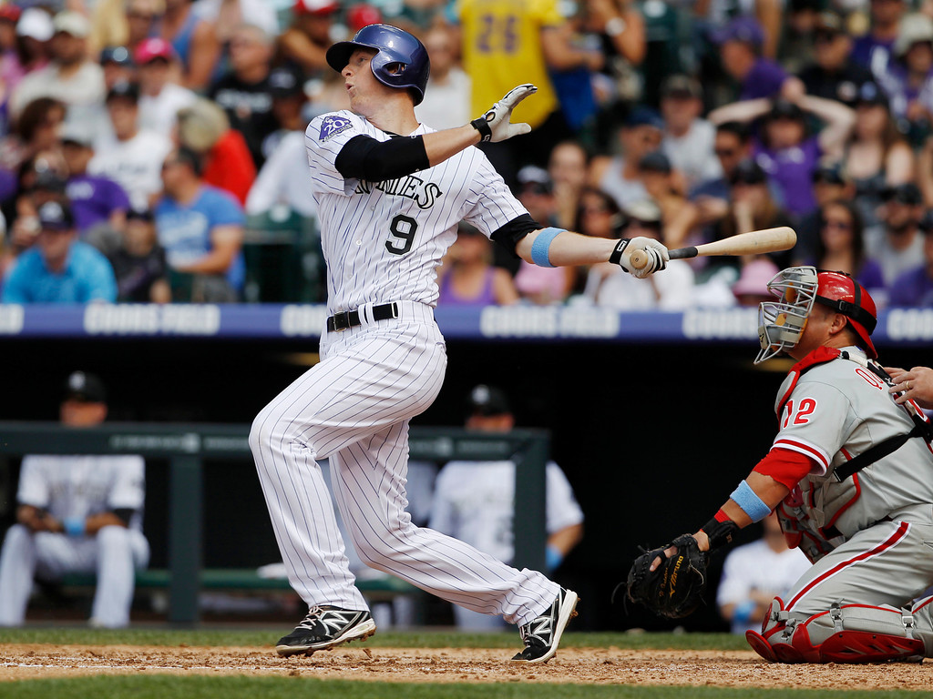 . Colorado Rockies\' DJ LeMahieu flies out as Philadelphia Phillies catcher Humberto Quintero looks on in the fifth inning of a baseball game in Denver on Sunday, June 16, 2013. (AP Photo/David Zalubowski)