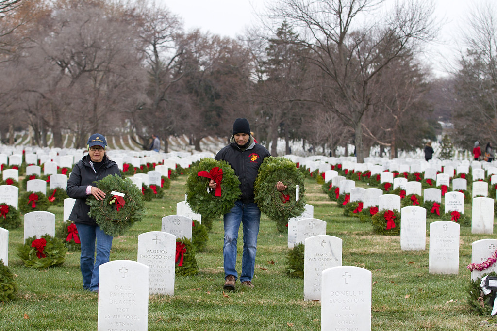 . Volunteer Marine Sgt. Jason Surratt help to lay holiday wreaths at graves at Arlington National Cemetery in Arlington, Va., Saturday Dec. 14, 2013, during Wreaths Across America Day. Wreaths Across America was started in 1992 at Arlington National Cemetery by Maine businessman Morrill Worcester and has expanded to hundreds of veterans\' cemeteries and other locations in all 50 states and beyond. (AP Photo/Jose Luis Magana)