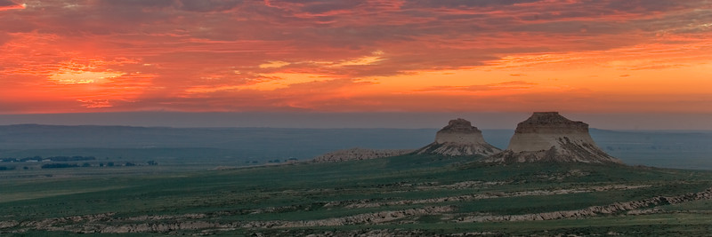 A colorful orange sunrise forms panorama as it spreads across the sky to greet the east and west buttes at Pawnee Buttes, in Pawnee National Grasslands, north of Greeley Colorado.