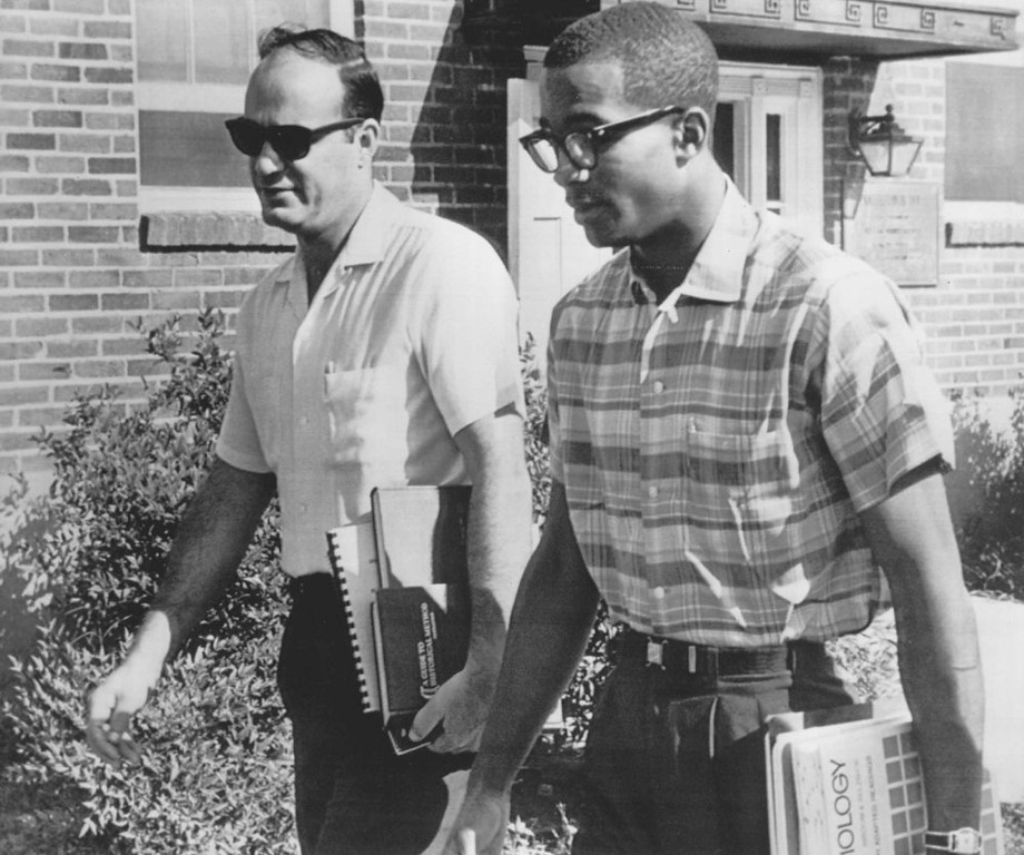 . James Hood is accompanied by Robert Davis, left, a white school teacher, as he walks to class at the University of Alabama at Tuscaloosa today. Davis, of Fort Walton Beach, Fla., is doing graduate work at the university. He greeted Hood warmly and chatted amicably with him en route to class. 1963