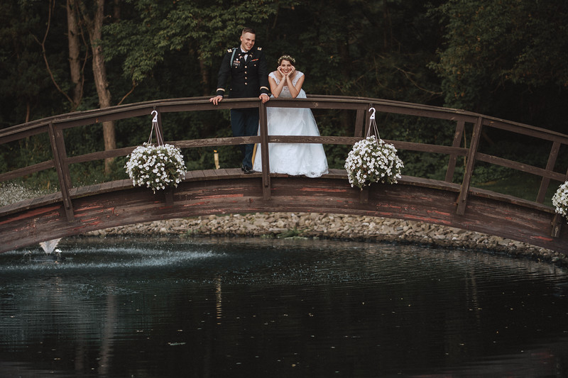 Bride and groom lean on the railing of a bridge over a pond. The bride rests her head on her hands and smiles.