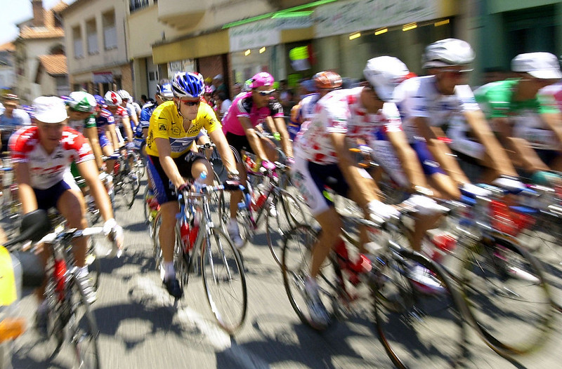 . Overall leader Lance Armstrong of Austin, Texas, center left with yellow jersey, rides with the pack at the start of the 13th stage of the Tour de France cycling race between Lavelanet and Beziers, southwestern France, Saturday, July 20, 2002. (AP Photo/Christophe Ena)