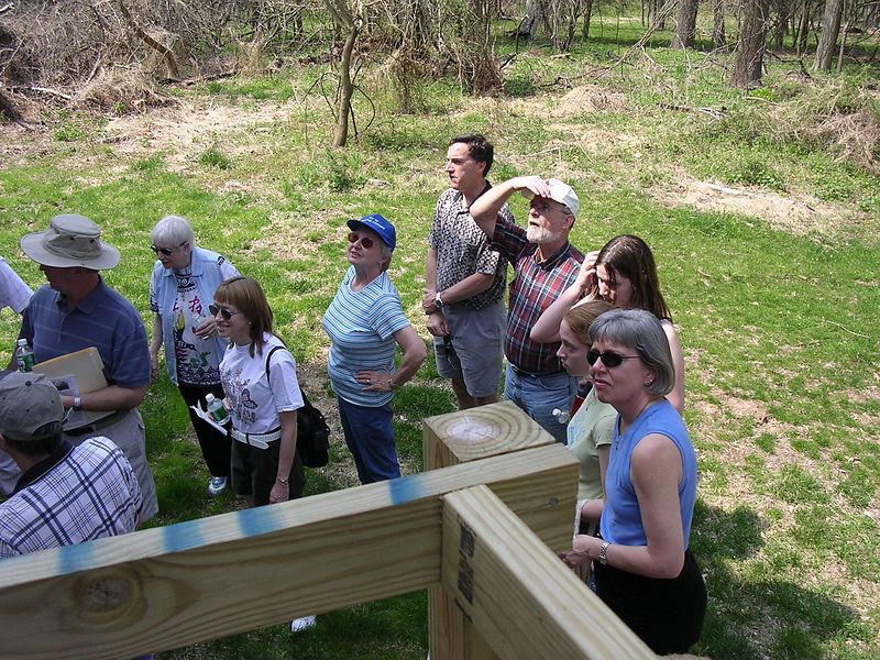 Some in the group look at other things, but all are fascinated by the old house.