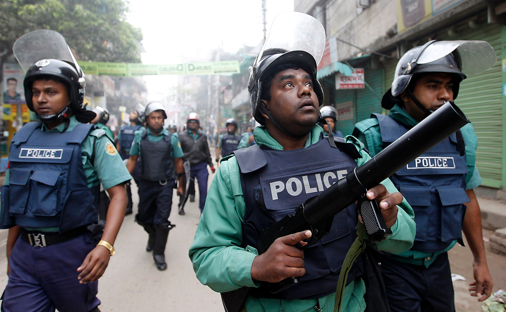 Description of . A police officer fires tear gas as they clash with activists of Bangladesh Nationalist Party during a strike in Dhaka on December 13, 2012. Bangladesh's opposition alliance, led by former Prime Minister Begum Khaleda Zia, called for an eight-hours nationwide strike, two days after another violent strike, to press home its demand for immediate release of its acting secretary general Mirza Fakhrul Islam Alamgir and in protest against the killings and arrests of opposition activists during their Sunday's road blockade program, local media reported.  REUTERS/Andrew Biraj