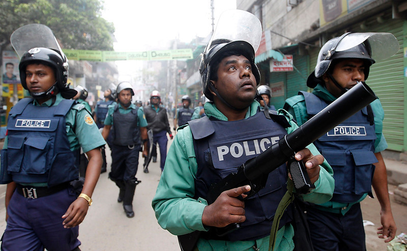 . A police officer fires tear gas as they clash with activists of Bangladesh Nationalist Party during a strike in Dhaka on December 13, 2012. Bangladesh\'s opposition alliance, led by former Prime Minister Begum Khaleda Zia, called for an eight-hours nationwide strike, two days after another violent strike, to press home its demand for immediate release of its acting secretary general Mirza Fakhrul Islam Alamgir and in protest against the killings and arrests of opposition activists during their Sunday\'s road blockade program, local media reported.  REUTERS/Andrew Biraj