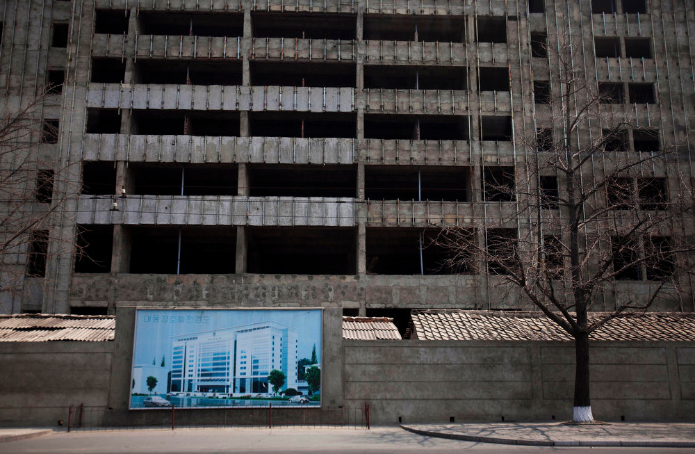 Description of . An illustration of a building project hangs in front of the construction project in progress in Pyongyang, North Korea on Wednesday, April 13, 2011.  (AP Photo/David Guttenfelder)