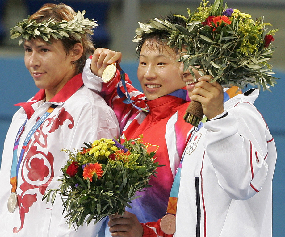 . Chinese wrestler Wang Xu (C), gold, Russian Gouzel Maniourova (L), silver, and Japanese Hamaguchi Kyoko pose on the podium after winning the women\'s 72KG wrestling final, at the Ano Liossia stadium at the 2004 Olympic Games, 23 August 2004 in Athens.  ANTONIO SCORZA/AFP/Getty Images