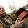 Tony Latter shows off the red maggots in a bait box.© 2010 Brian Gay