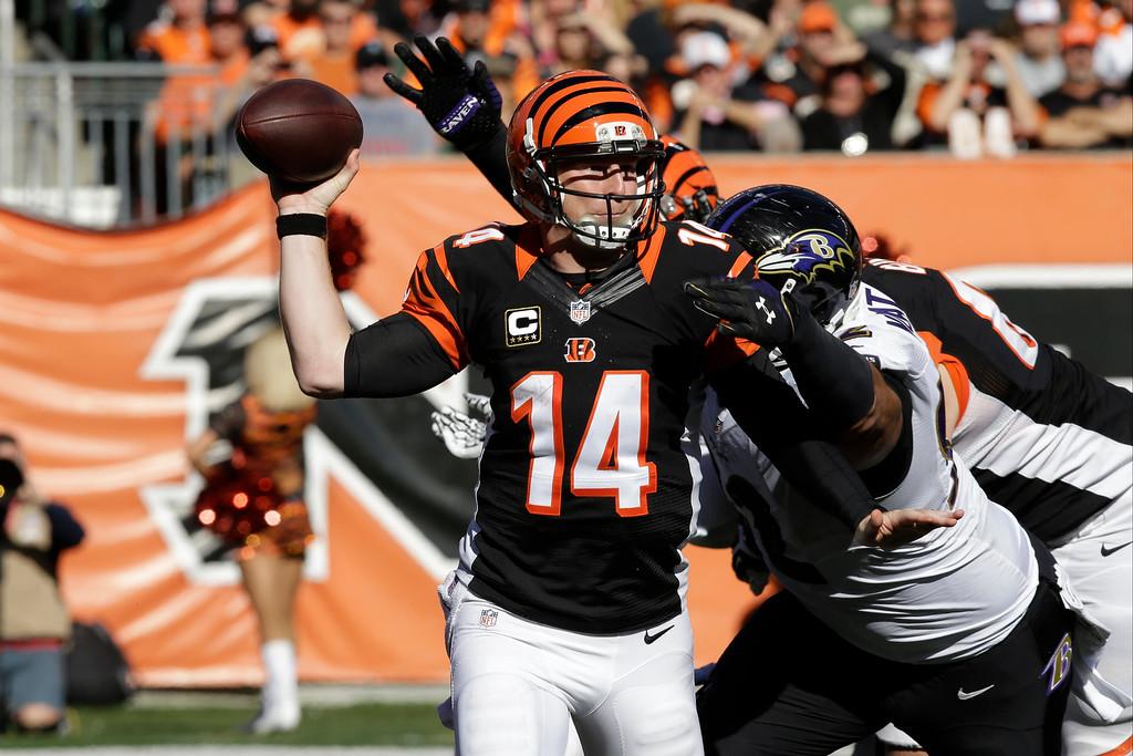 . Cincinnati Bengals quarterback Andy Dalton, left, is pressured by Baltimore Ravens defensive end Haloti Ngata during the second half of an NFL football game in Cincinnati, Sunday, Oct. 26, 2014. (AP Photo/Al Behrman)