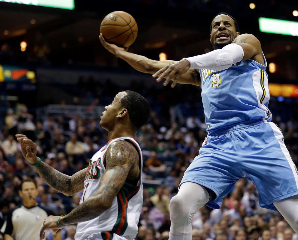 . Denver Nuggets\' Andre Iguodala, right, drives against Milwaukee Bucks\' Monta Ellis, left, during the first half of an NBA basketball game on Monday, April 15, 2013, in Milwaukee. (AP Photo/Jeffrey Phelps)