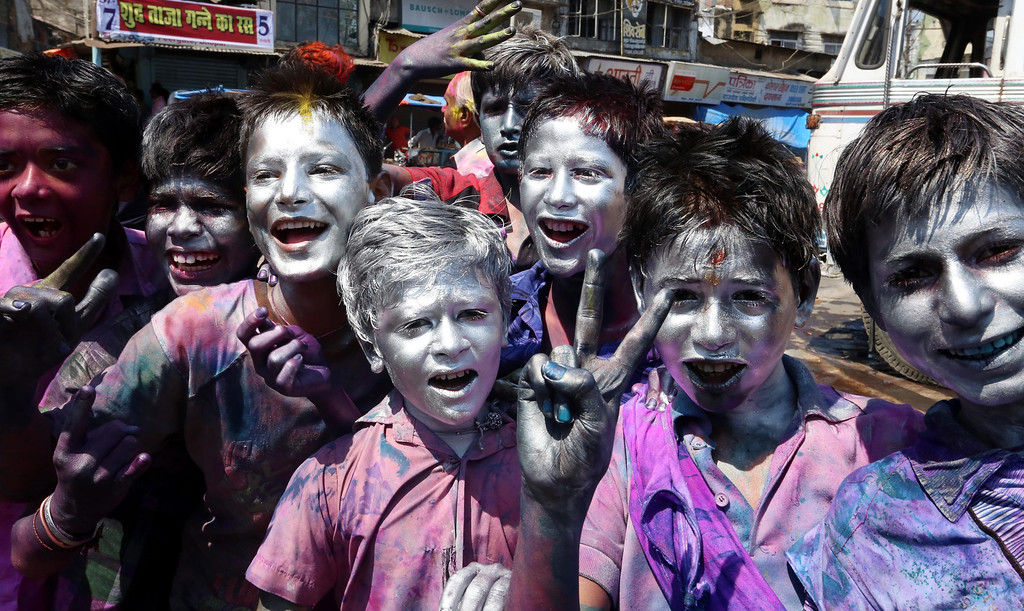 . Children smeared with silver colour pose for photographs during a procession on the occasion of Holi, festival of colors in Bhopal, India, 17 March 2014. Holi is the Hindu spring festival of colors, celebrated with full zeal and fervour.  EPA/SANJEEV GUPTA