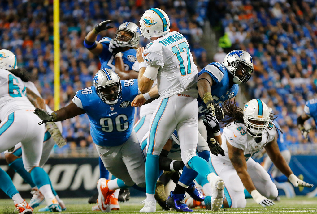 . Miami Dolphins quarterback Ryan Tannehill (17), rushed by Detroit Lions defensive tackle Andre Fluellen (96), and cornerback Rashean Mathis (31), passes, during the second half of an NFL football game in Detroit, Sunday, Nov. 9, 2014. (AP Photo/Paul Sancya)