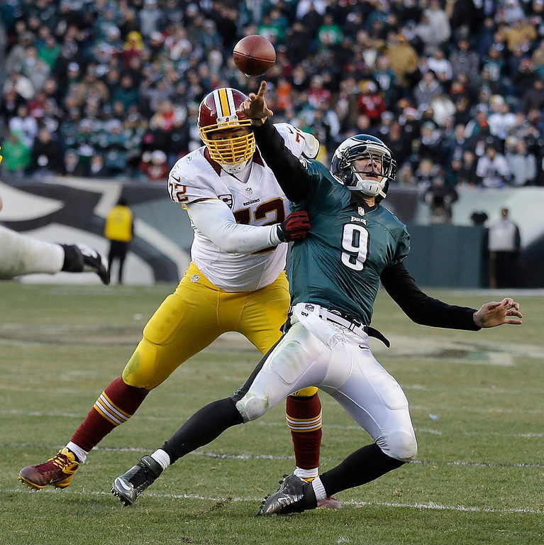 . Philadelphia Eagles\' Nick Foles passes the ball as Washington Redskins\' Stephen Bowen brings him down during the final seconds of an NFL football game, Sunday, Dec. 23, 2012, in Philadelphia. Foles was called for intentional grounding on the game-ending play. Washington won 27-20. (AP Photo/Mel Evans)