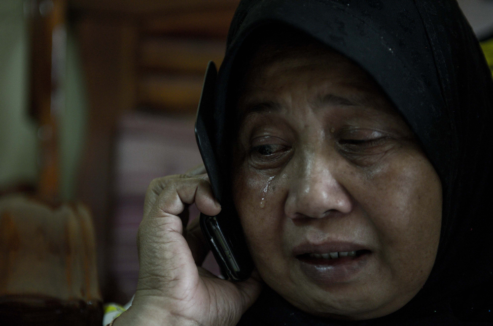 . A relative of Norliakmar Hamid and Razahan Zamani, passengers on a missing Malaysia Airlines Boeing 777-200 plane, cries at their house in Kuala Lumpur on March 8, 2014. Malaysia and Vietnam on March 8 led a search for a Malaysia Airlines jet that has gone missing over Southeast Asia, as fears mounted over the fate of the 239 people aboard. (MOHD RASFAN/AFP/Getty Images)