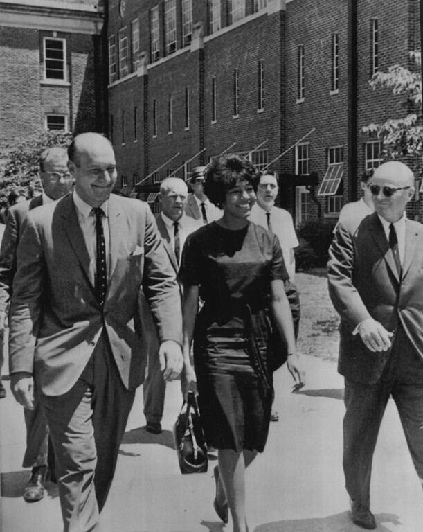 . Vivian Malone flashes a wide grin as she is escorted to her dormitory, Mary Burke Hall, after being stopped at the door of the University of Alabama at Tuscaloosa today. Background is Foster Auditorium where Gov. George Wallace made his defiant stand. At left is Nicholas Katzenbach, deputy U.S. attorney general. 1963  (The Denver Post Archive)