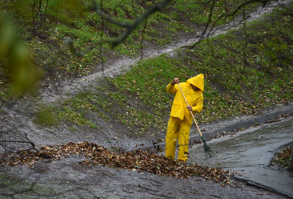 . Maintenance worker Sandro Arias rakes leaves away from the downhill flow of water on the hill near Mount Diablo Elementary in Clayton, Calif., Thursday, Dec. 11, 2014. (Susan Tripp Pollard/Bay Area News Group)