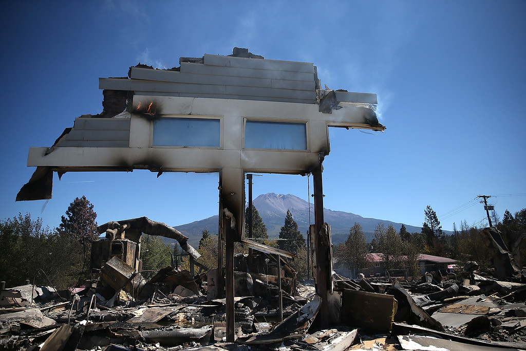 . A section of a structure stands over the remains of destroyed business on September 16, 2014 in Weed, California. A fast moving wildfire fueled by high winds ripped through the town of Weed on the afternoon of September 15, burning 100 structures including the high school and lumber mill.  (Photo by Justin Sullivan/Getty Images)