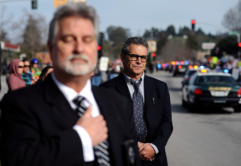. Retired Lt. Ken Knuth, left, stands in salute as the procession for detectives Sgt. Loran \'Butch\' Baker and Elizabeth Butler moves down Ocean Street in Santa Cruz, Calif., on Thursday morning, March 7, 2013. (Matthew Hintz/Santa Cruz Sentinel)