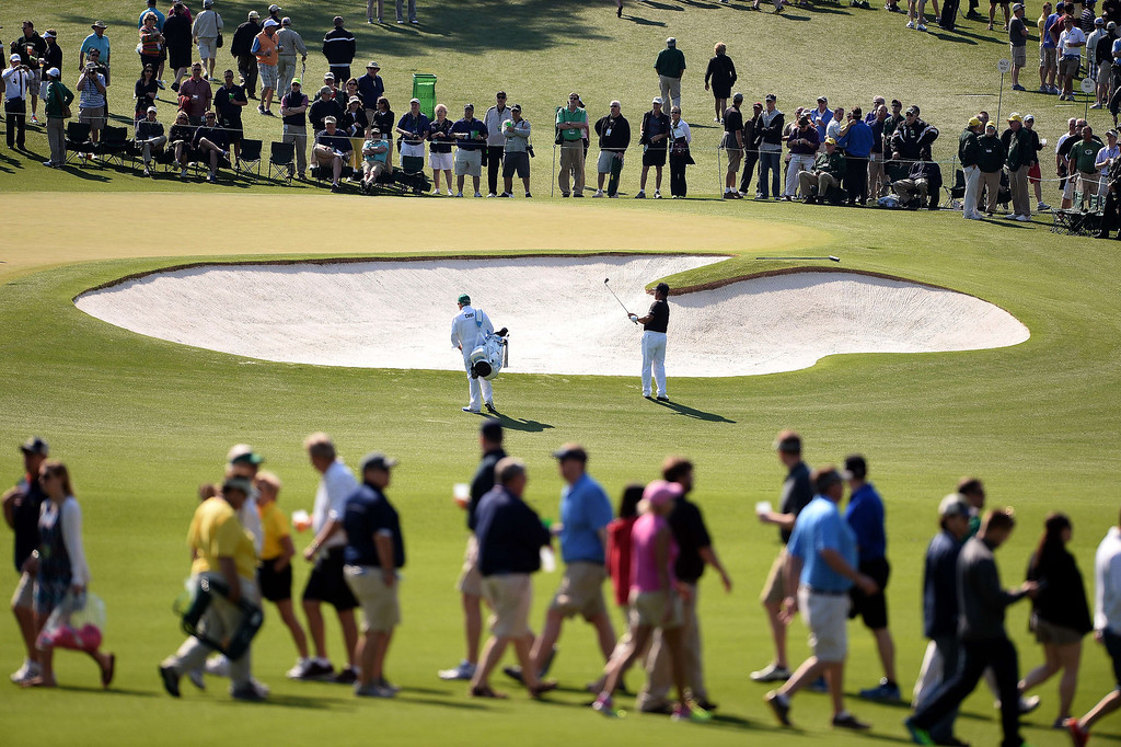 . K. J. Choi of South Korea (C) plays a shot as patrons make their way during a practice round prior the start of the 78th Masters Golf Tournament at Augusta National Golf Club on April 09, 2014 in Augusta, Georgia. Augusta National\'s trademark back-nine drama in the final round of the Masters could reach epic heights Sunday with a field that offers no clear favorite and several rising young stars.  EMMANUEL DUNAND/AFP/Getty Images