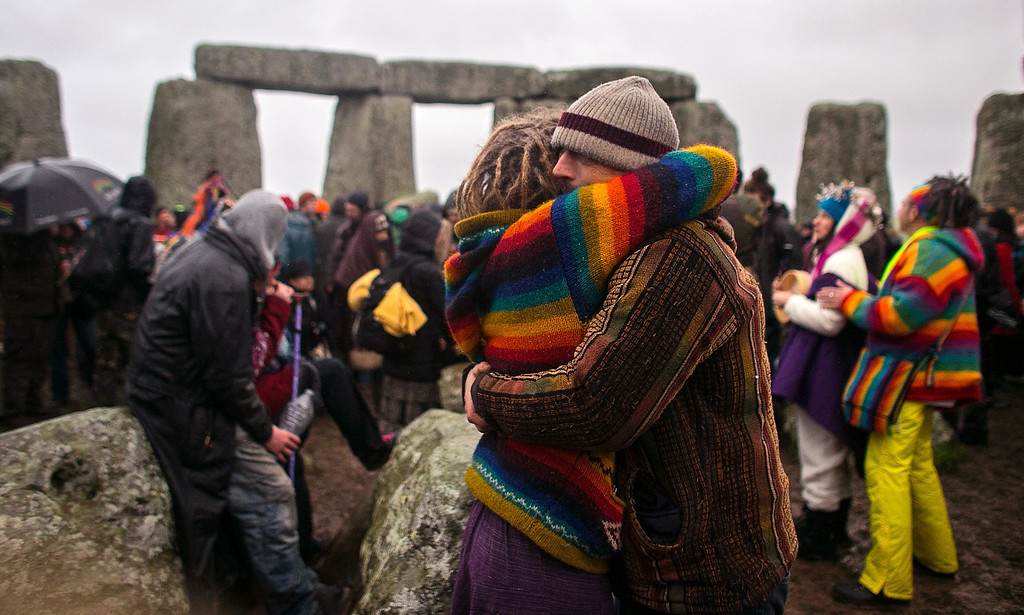 . A couple embrace as druids, pagans and revelers gather in the centre of Stonehenge, hoping to see the sun rise, as they take part in a winter solstice ceremony at Stonehenge on December 21, 2013 in Wiltshire, England. Despite the rain and wind, a large crowd gathered at the famous historic stone circle to celebrate the sunrise closest to the Winter Solstice, the shortest day of the year - an event claimed to be more important in the pagan calendar than the summer solstice, because it marks the \'re-birth\' of the Sun for the New Year.  (Photo by Matt Cardy/Getty Images)