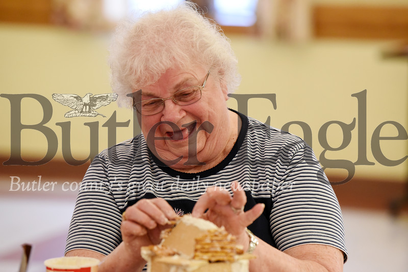 Harold Aughton/Butler Eagle: Ella Mae Smith of Evans City places pretzels on the roof of her gingerbread house at the Senior Center, Tues., Nov. 3, 2019.