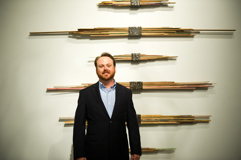 Artisit Pual Seeman standing in front of one of his large pieces hanging in the Weil Gallery