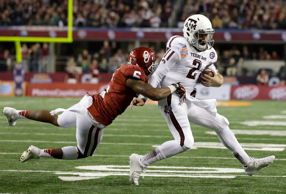 Description of . Oklahoma 's Demontre Hurst (6) brings down Texas A&M's Johnny Manziel after a short run shy of the end zone in the second half of the Cotton Bowl NCAA college football game Friday, Jan. 4, 2013, in Arlington, Texas. (AP Photo/Tony Gutierrez)