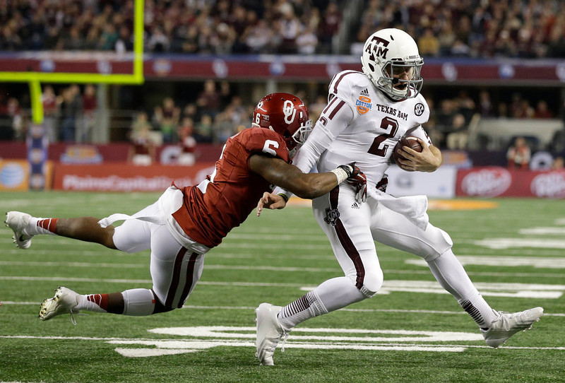 . Oklahoma \'s Demontre Hurst (6) brings down Texas A&M\'s Johnny Manziel after a short run shy of the end zone in the second half of the Cotton Bowl NCAA college football game Friday, Jan. 4, 2013, in Arlington, Texas. (AP Photo/Tony Gutierrez)