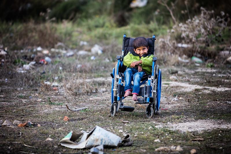 A young boy smiling in a wheelchair sits on the edge of the refugee camp where he lives. Bekaa Valley, Lebanon. November 2015. ----------- Un jeune garçon en fauteuil roulant sourit à l'écart du camp de réfugiés où il habite. Vallée de la Bekaa, Liban. Novembre 2015.
