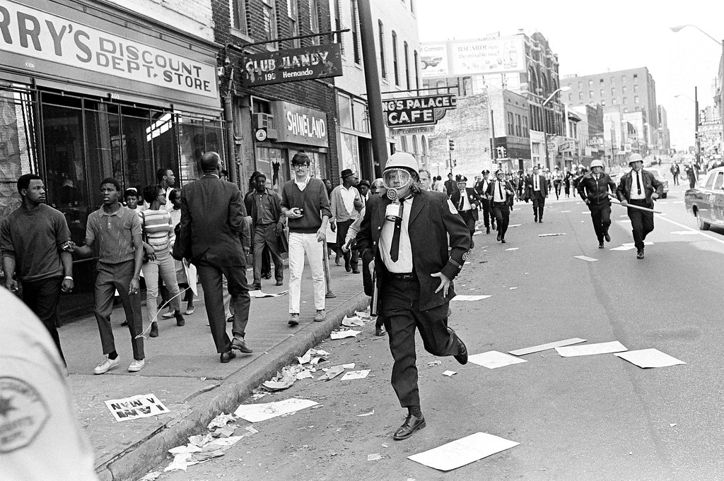 . Police patrol streets littered with broken glass and placards in the riot-torn sector of downtown Memphis, Tenn., March 28, 1968. Violence erupted midway through a march led by Dr. Martin Luther King Jr., in support of striking garbage workers. Police broke it up with tear gas and batons. (AP Photo/Jack Thornell)