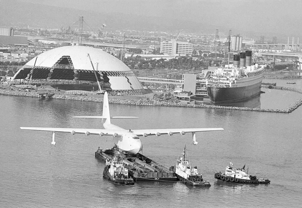 ". ""Spruce Goose,\"" the flying boat that belonged to the late millionaire Howard Hughes, sits perched on a barge as it was eased across the harbor in Long Beach, Calif., Feb. 11, 1982, on the way to its new display home, the large aluminum dome in left background.  At right background is the former luxury liner Queen Mary, its decks filled with sightseers watching the cross-channel move.  (AP Photo/Wally Fong)"